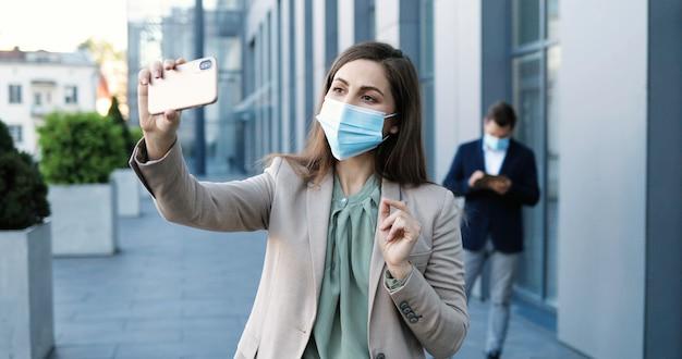 ビジネスビルで屋外のスマートフォンでビデオチャットをしている医療マスクのかなり幸せな白人の若い女性。携帯電話のウェブカメラを介して話したりビデオチャットしたりする陽気な美しい女性。