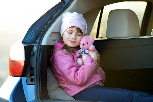 Очень счастливая девушка ребенка играя при розовый плюшевый медвежонок игрушки сидя в багажнике автомобиля.