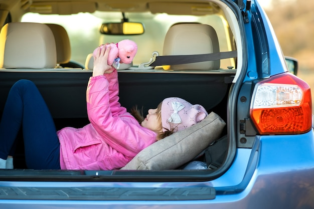 Pretty happy child girl playing with a pink toy teddy bear in a car trunk.