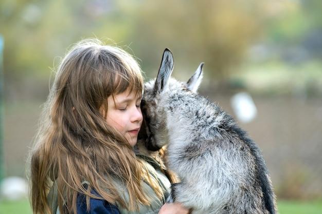농장 마당에서 작은 아이 염소와 함께 연주 꽤 행복 한 아이 소녀.
