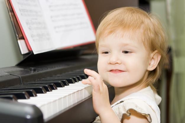 꽤 행복한 아이가 실내에서 피아노를 친다