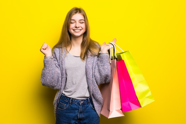 Pretty happy ecxited teenage girl with color shopping bags