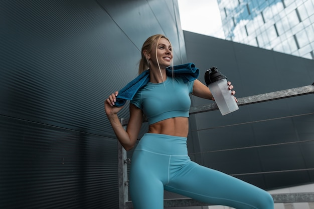 현대적인 도시에 셰이커 병과 수건이 있는 패션 파란색 운동복을 입은 슬림한 몸매를 가진 꽤 행복한 피트니스 모델 소녀