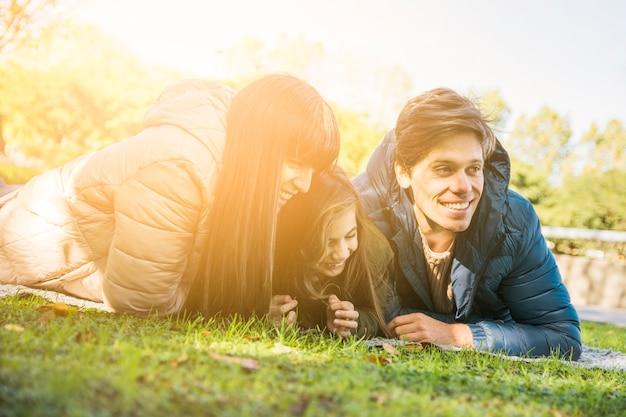 Довольно счастливая девушка, наслаждаясь в парке с ее матерью и отцом