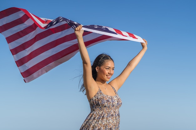 Pretty and happy girl holds a flag of the united states against the sky.