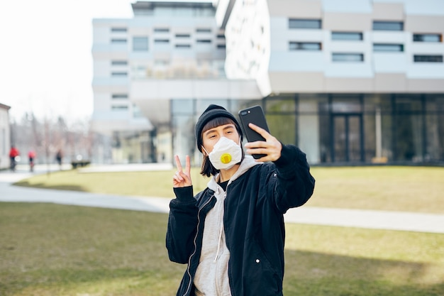 Довольно счастливая девушка в повседневной одежде и с респираторной маской делает селфи на улице во время пандемии коронавируса
