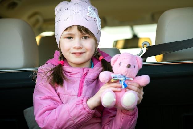 Pretty happy girl playing with a pink teddy bear sitting in a car trunk