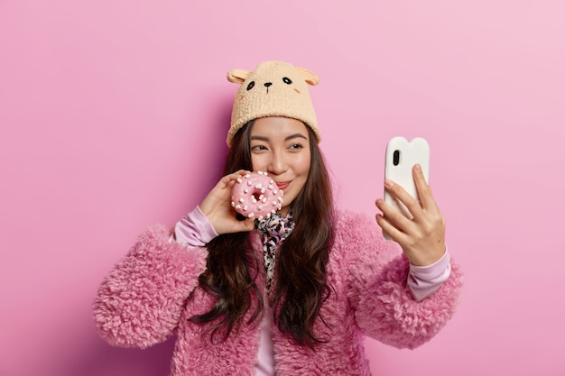 Pretty happy korean girl poses with freshly baked doughnut, takes selfie portrait, unhealthy eating, shares photos in social networks