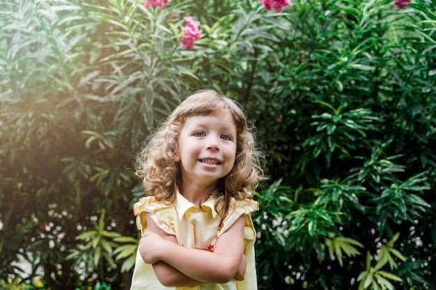 Pretty happy little girl in a yellow dress in green beautiful garden outdoor