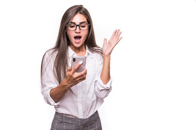 白い壁に携帯電話でポーズをとってかなり幸せな驚きの女性