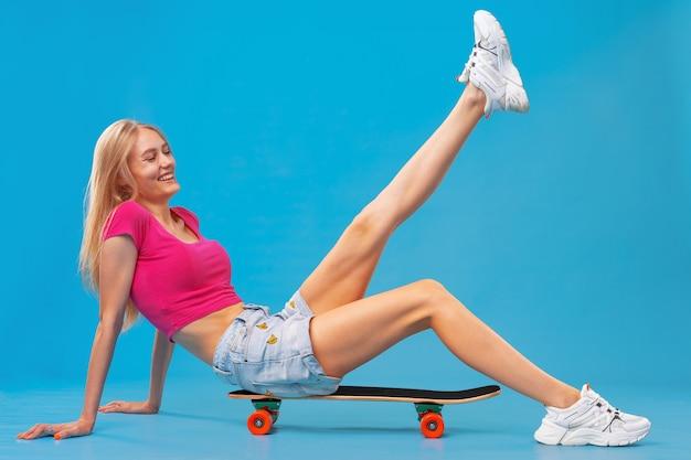 Довольно счастливая женщина, небрежно одетая, сидит на скейтборде