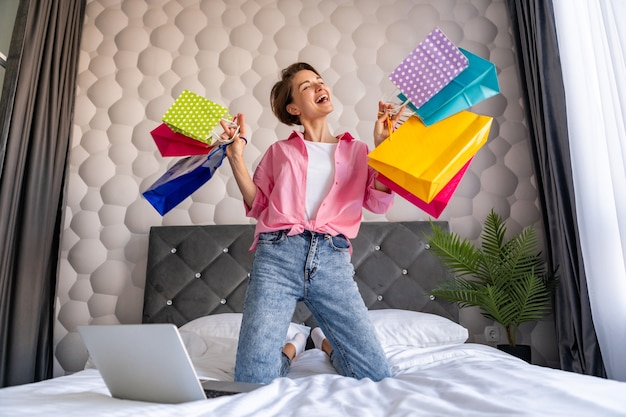 Pretty happy woman having fun jumping on bed at home with colorful shopping bags