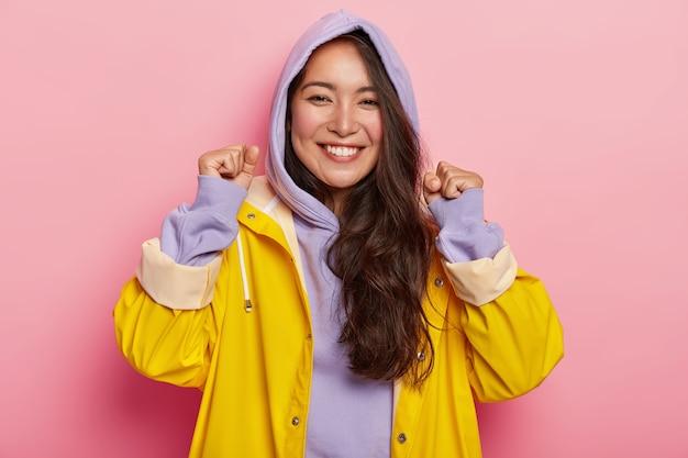 La donna abbastanza felice alza i pugni chiusi, esprime emozioni positive, ha una bellezza naturale, vestita con abiti casual, impermeabile per tempo piovoso, sorride ampiamente