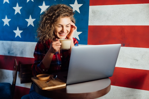 Pretty, happy woman using laptop while sitting at cafe. young woman sitting in a coffee shop and working on laptop.