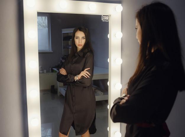 大きな鏡で自分を見つめているかなり幸せな女性。女性は休日の服を選びます