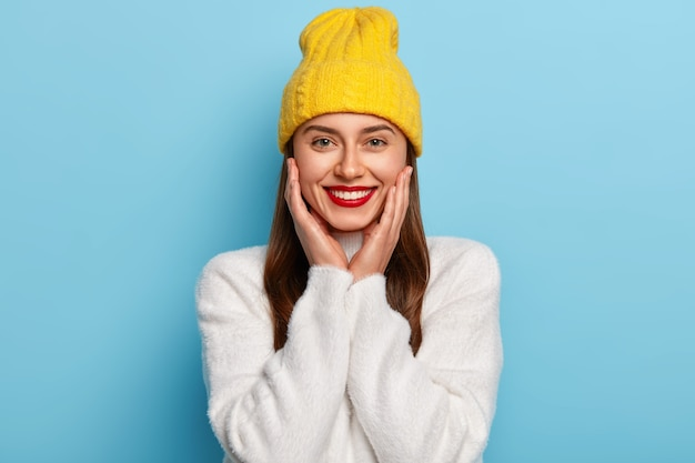 Pretty happy woman wears red lipstick, keeps hands on cheeks, wears yellow hat and white cashemere sweater, poses against blue wall