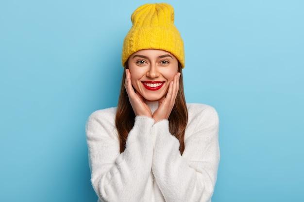 La donna abbastanza felice indossa il rossetto rosso, tiene le mani sulle guance, indossa un cappello giallo e un maglione di cashmere bianco, posa contro il muro blu