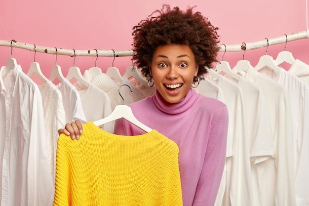 아프로 머리를 가진 꽤 행복한 여자, 옷걸이에 밝은 노란색 스웨터를 보유하고, 옷차림을 집어 들고, 집 옷장 근처에 서 있습니다.