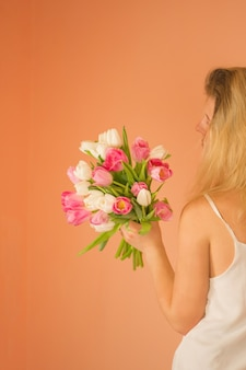 Pretty happy woman with long blond hair holding tulip bouquet.  portrait of a cheerful young girl in dress  with bouquet of flowers.