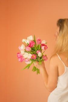 チューリップの花束を保持している長いブロンドの髪を持つかなり幸せな女性。花の花束とドレスを着て陽気な少女の肖像画。
