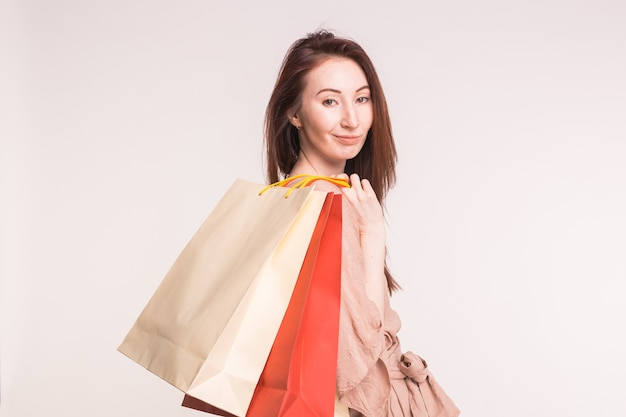白い壁に紙袋で購入してかなり幸せな若いアジアの女性