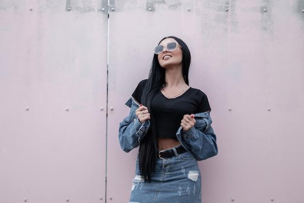 선글라스 빈티지 청바지 스커트에 트렌디 한 블랙 탑에 세련된 데님 재킷에 미소로 꽤 행복 젊은 힙 스터 여자는 도시의 벽 근처 이완. 긴 머리를 가진 즐거운 갈색 머리 소녀