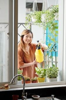 Довольно счастливая молодая женщина поливает растения и цветы на подоконнике своего дома