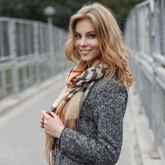 세련된 스카프와 트렌디 한 코트에 아름다운 미소로 꽤 행복한 젊은 여자가 빈티지 금속 울타리 근처 도시를 산책