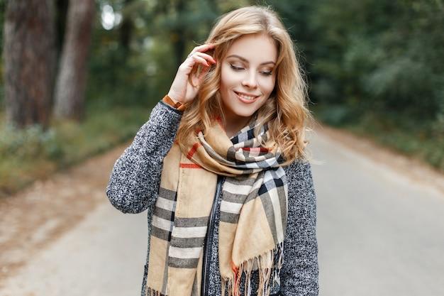체크 무늬 베이지 스카프에 세련된 빈티지 코트에 예쁜 미소로 꽤 행복한 젊은 여자가 따뜻한 봄 날에 공원에서 산책