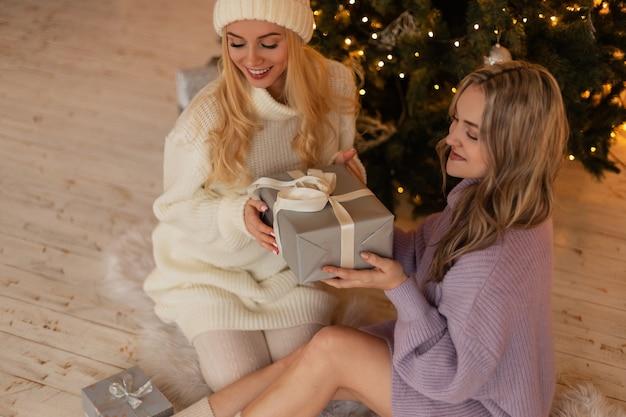 自宅のクリスマスツリーの近くに座っているセーターと贈り物の帽子とファッショナブルなニットの服を着て笑顔でかなり幸せな若い女性。冬休み