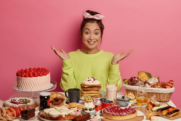 Pretty hesitant woman doesn't want what to taste first, spreads palms, wears green jumper, has sweet nutrition, gets much calories, degustates various homemade confectionery