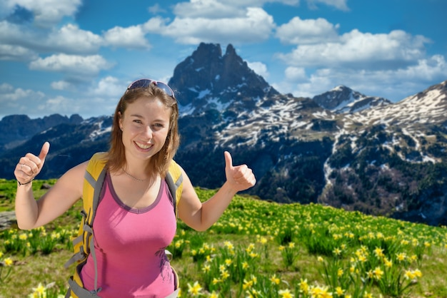 Pretty hiker woman with pic du midi ossau and daffodils in pyrenees