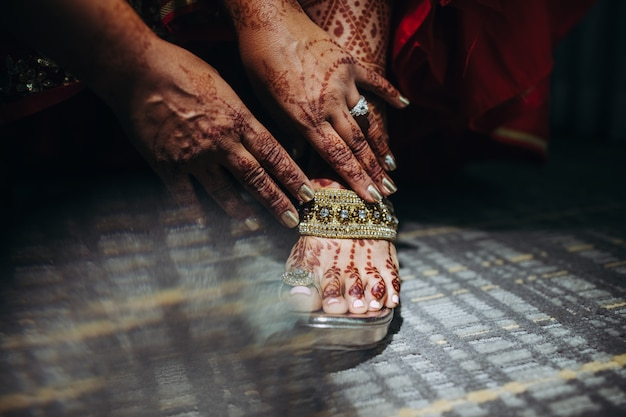 Pretty hindu bride puts on her wedding shoes