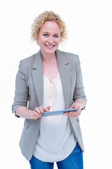 Pretty hipster smiling at camera and holding tablet