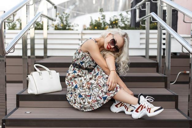 Симпатичная хипстерская стильная женщина в солнцезащитных очках в модном винтажном платье с кроссовками и сумкой сидит на ступеньках.