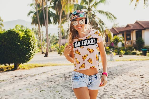 アクセサリーキャップサングラスを身に着けて、楽しんで笑って、晴れた夏の熱帯の休暇でスタイリッシュなカラフルな衣装でヘッドフォンで音楽を聴いてビーチダンスを歩いているかなり流行に敏感な女性