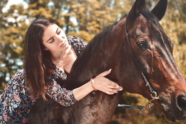 Pretty hispanic brunette giving her horse a hug while riding him in the forest. love animals concept. love horses