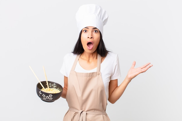 Pretty hispanic chef woman amazed, shocked and astonished with an unbelievable surprise and holding a noodle bowl