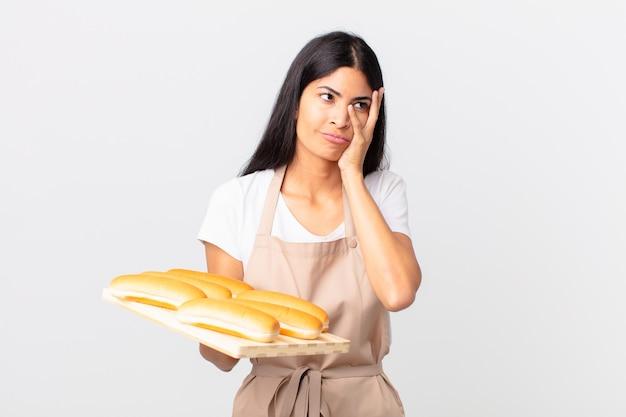 Довольно латиноамериканская женщина-повар чувствует скуку, разочарование и сонливость после утомительного и держит поднос с хлебными булочками