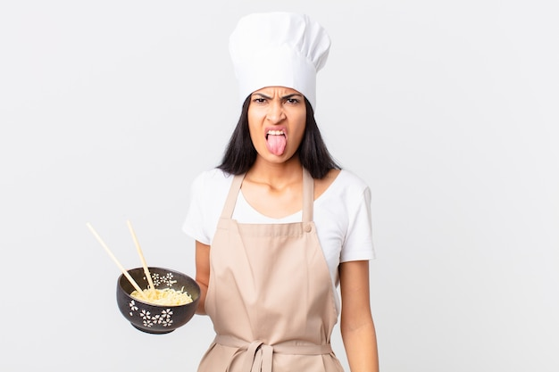 Pretty hispanic chef woman feeling disgusted and irritated and tongue out and holding a noodle bowl