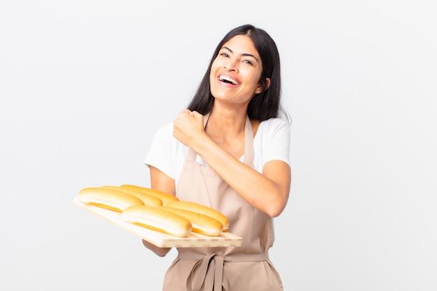 예쁜 히스패닉 셰프 여성은 행복하고 도전에 직면하거나 빵이 든 쟁반을 들고 축하하고 있습니다