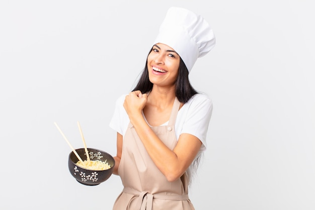 Pretty hispanic chef woman feeling happy and facing a challenge or celebrating and holding a noodle bowl