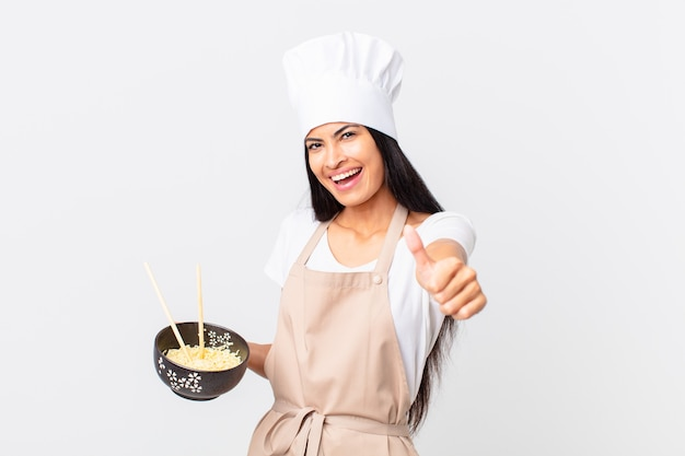 Pretty hispanic chef woman feeling proud,smiling positively with thumbs up and holding a noodle bowl
