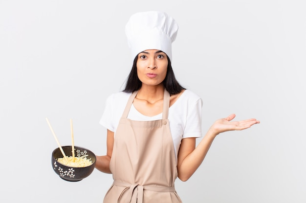 Pretty hispanic chef woman feeling puzzled and confused and doubting and holding a noodle bowl