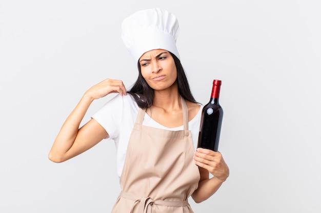 Довольно латиноамериканская женщина-повар чувствует стресс, тревогу, усталость и разочарование и держит бутылку вина