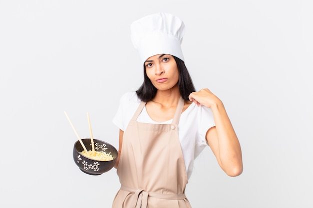 Pretty hispanic chef woman looking arrogant, successful, positive and proud and holding a noodle bowl