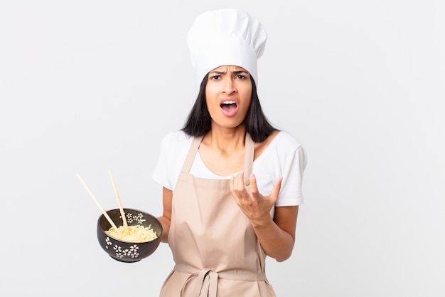 Pretty hispanic chef woman looking desperate, frustrated and stressed and holding a noodle bowl