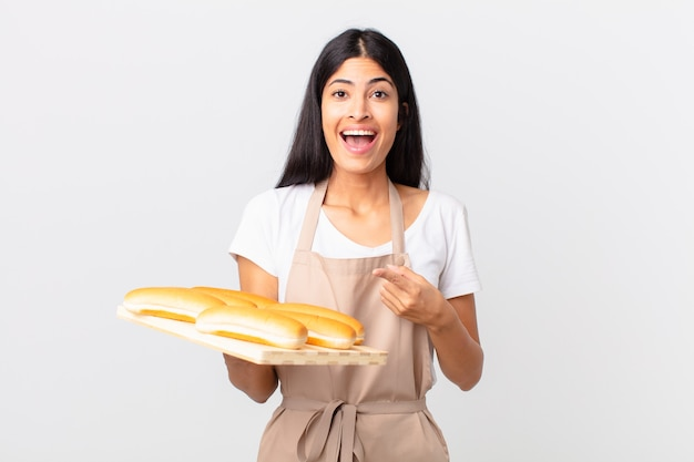 Pretty hispanic chef woman looking excited and surprised pointing to the side and holding a tray with bread buns