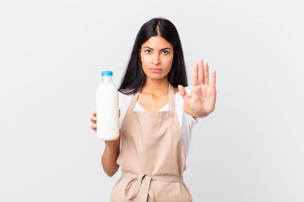 Довольно латиноамериканский шеф-повар выглядит серьезным, показывая открытую ладонь, делая жест остановки и держа бутылку молока