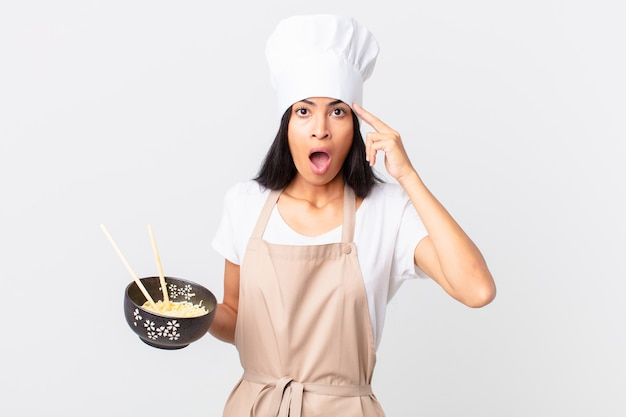 Pretty hispanic chef woman looking surprised, realizing a new thought, idea or concept and holding a noodle bowl